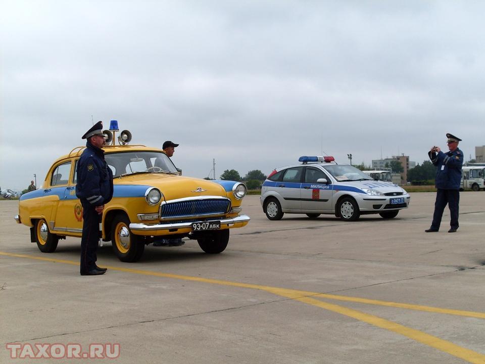 Сотрудник ГИБДД фотографирует своего коллегу рядом с советским милицейским автомобилем