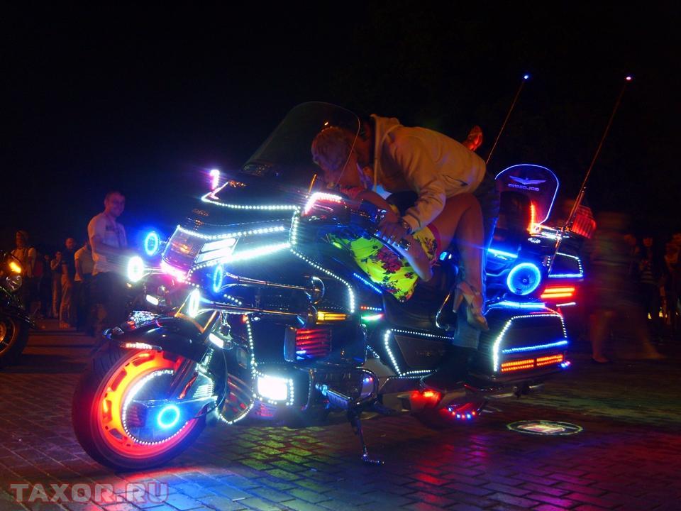 Ярко подсвеченный мотоцикл на тусовке байкеров