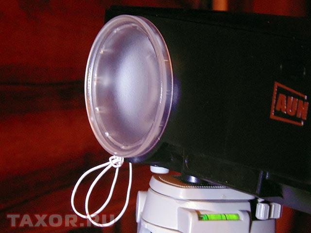 Крышка объектива крепится к проектору шнурком