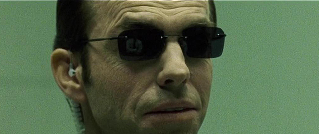 В отражении солнцезащитных очков Смита виден спокойно сидящий напротив Нео